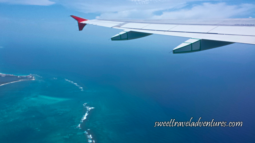 Left Airplane Wing Flying Above Blue-Green Sea With Blue Sky and White Fluffy Clouds