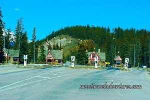 Road with four lanes and a small brown wooden building next to each lane, each building has a Canadian flag on the top of it, evergreen trees and mountains in the background, and a clear blue sky except for one small and faint white cloud on the left-hand side