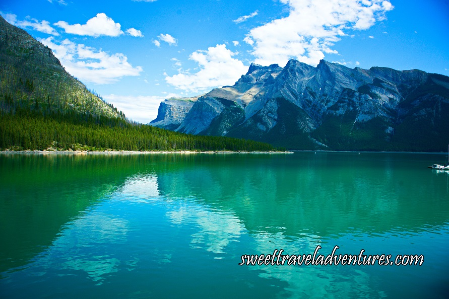 Blue cloudy sky, grey mountains, and green grass reflecting on a calm blue lake