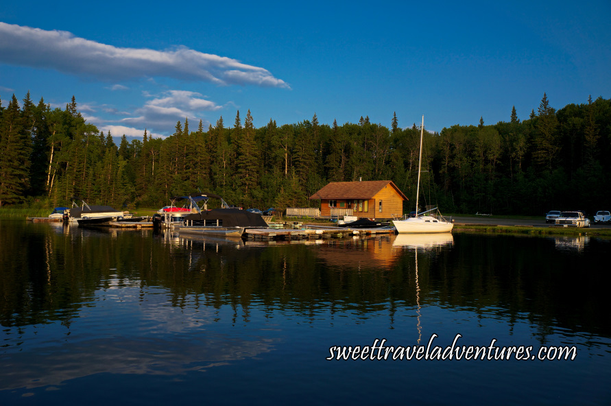 Small marina with boats with tall trees behind it and a blue sky with a few fluffy white clouds reflected on the water