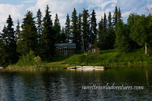 A wooden cabin nestled between trees with a miniature cabin to the right on a grassy shore with a small dock, rippled water, and a blue sky filled with large fluffy white clouds