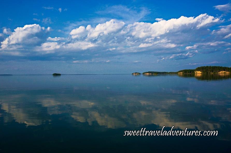 Islands with trees and blue sky with large fluffy white clouds all reflected on calm lake