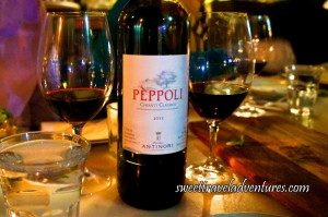 A Bottle of Chianti Wine on a Table With Two Glasses Filled With Wine Next to it (One on Either Side)