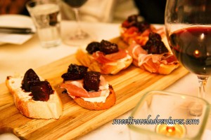 A Wooden Cutting Board Angled on a Table With Five Slices of Grilled Baguette, Each With Two Pieces of Fig on Top of Prosciutto, Which is on Top of Mascarpone and a Tealight Candle in a Square Glass Votive as well as a Glass of Red Wine Next to the Wooden Board