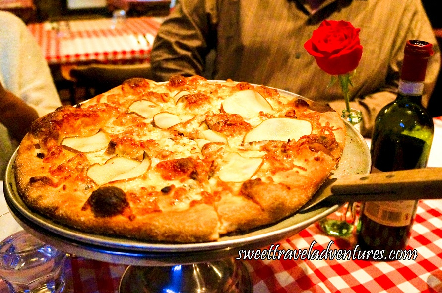 A Pizza Server Placed Under a Pizza With Thin Slices of Pear and Covered in Cheese Sitting on a Silver Platter Stand on a Table With a Red and White Checkered Table Cloth Next to a Bottle of Wine and a Red Rose Placed in an Old Glass Coke Bottle