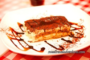 A Fluffy White Rectangular Dessert With a Dark Brown Layer on Top, on A White Plate With Golden Brown Liquid Swirls Around the Plate and Some Golden Brown Liquid Across the Top of the Dessert