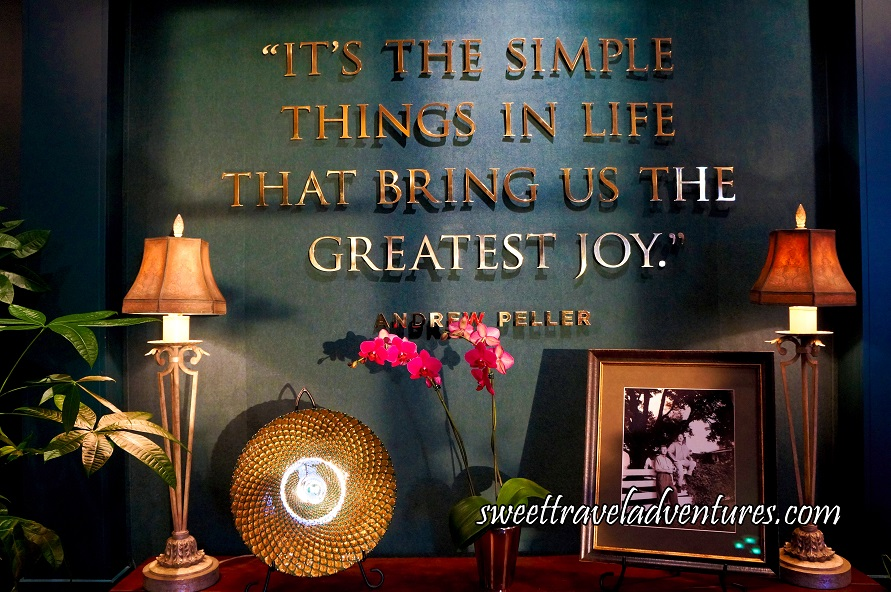 A Quote in Gold Lettering Saying It's the Simple Things in Life That Brings Us the Greatest Joy on a Dark Green Wall With Decorations on a Wooden Table Below the Quote