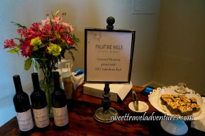 A Wooden Table With Caramel Brownies on the Right-Hand Side on a White Cake Platter and Covered With a Glass Cover and Three Bottles of Red Wine on the Left With a Bouquet of Pink and Yellow Flowers in a Glass Vase Behind the Wine and a Sign Describing the Pairing in the Middle