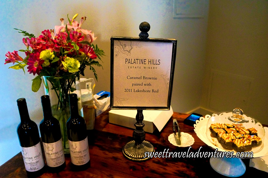 A Wooden Table With Caramel Brownies on the Right-Hand Side on a White Cake Stand and Covered With a Glass Cover and Three Bottles of Red Wine on the Left With a Bouquet of Pink and Yellow Flowers in a Glass Vase Behind the Wine and a Sign Describing the Pairing in the Middle