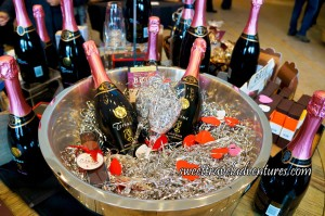 Two Bottles of Sparkling Wine in a Silver Party Tub With Silver String Confetti, Red and Pink Hearts, and Two Champagne Flutes With a Chocolate Behind the Bottles and a Box of Ice Wine Chocolates on the Left-Hand Side of the Party Tub