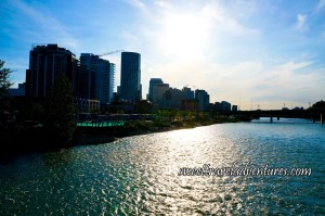 Blue Sky With the Sun Shining Overhead and Reflecting on the Blue Water, a Small Bridge in the Distance on the Right, and Tall Buildings on the Left With Green Trees Next to the River