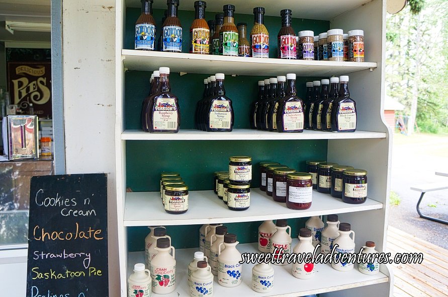 White Shelves With a Dark Green Back Panel and the Top Row of Gordo's Sauces and Spices, Below that a Row of Syrups, Below that a Row of Jams, Below that a Row of Ciders