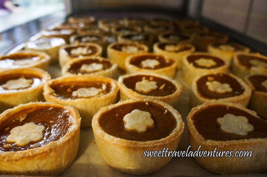 Several Golden-Brown Buttertarts Filled With Orange-Brown Filling and a Flower Shaped Golden-Brown Centre on a Silver Tray