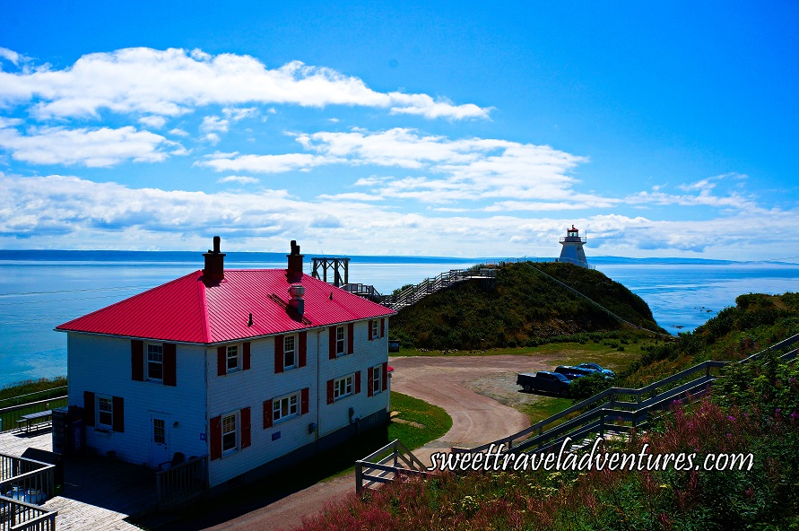 A Blue Sky With Long Fluffy White Clouds and on the Left There is a Large White Building With a Red Roof and Red Shutters and to the Right There is a Wooden Staircase and Grass and in the Middle There is a Grassy Hill With a White Lighthouse on Top Looking Out at the Blue Water