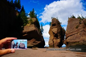 A Blue Sky With Two Huge Fluffy White Clouds and Three Huge Brown Rocks With the Middle One Facing Us Which Looks Like an Elephant Except the Trunk is Missing and There is a Sandy Brown Floor, the View is the Same as the Picture on a New Brunswick Health Care Card that is Being Held Next to it