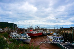 A Sky Filled With Fluffy Greyish White Clouds, Fishing Boats Sitting on a Muddy Ocean Floor With a Wharf on the Right and Left of the Boats, Green Plants to the Left and Green Grass and Trees Next to the Wharf on the Left, and Blue Water in the Distance