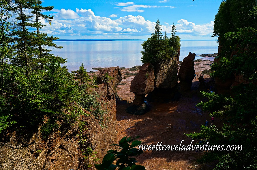 Two Brown Rocks Forming an Arch With Green Trees Growing From the Top of It and a Tall Thin Rock to the Right of it on a Muddy Beach With A Cliff on Either Side With Green Trees, Blue Water in the Distance and a Sunny Blue Sky With Fluffy White Clouds