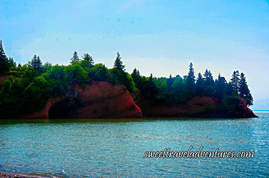 Large Reddish Brown Rock With an Opening and Green Trees Growing Out of the Top of the Rock, Fairly Calm Blue Water and a Light Blue Sky