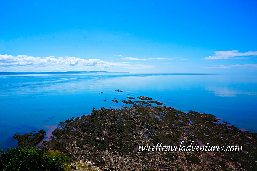 Brown Rocks Jutting Out into the Blue Water and Blue Sky With Long Fluffy White Clouds to the Left of the Horizon