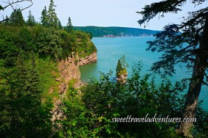 Calm Aqua Blue Water With a Large Rock Close to the Shoreline With Trees Growing From the Top, Rocky Cliffs and Coastline and Many Green Trees
