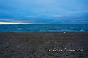 Sun Beginning to Set on Blue Water With Small Waves, Wide Sandy Beach With Yellow Float Board