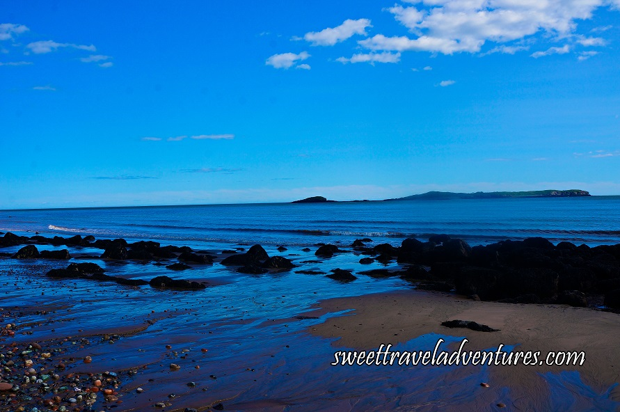 Blue Sky With a Few Fluffy White Clouds and Blue Ocean Water, Land in the Distance Covered in Greenery, A Few Small Waves Close to Shore, Water Washing Up on the Sandy Beach, Large Rocks Covered in Black Seaweed on the Beach With A Big Cluster of Them to the Right, Some Pebbles of Different Colours to the Left