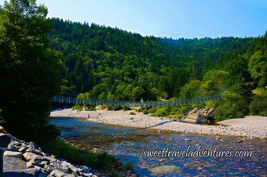 A Long Suspension Bridge With People on it Over a River, Water is Clear and You can See the Rocky Bottom, Shore on Both Sides of the River is Filled With Large Rocks, People in the Distance on the Farthest Shoreline, Many Green Trees All Around and a Blue Sky