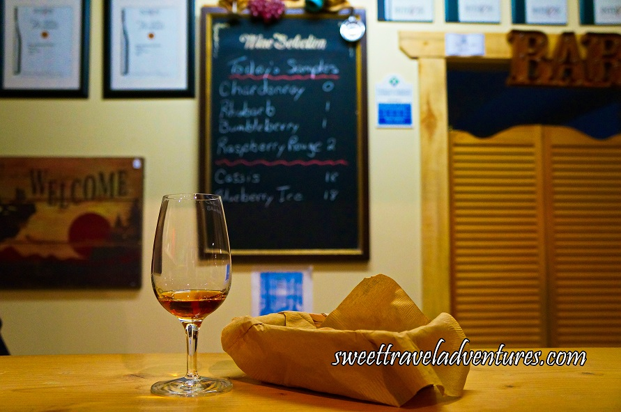 A Small Glass of Wine Next to a Napkin Covered Basket on a Narrow Wooden Table With a Chalkboard, Awards, and Welcome Sign on the Wall Behind