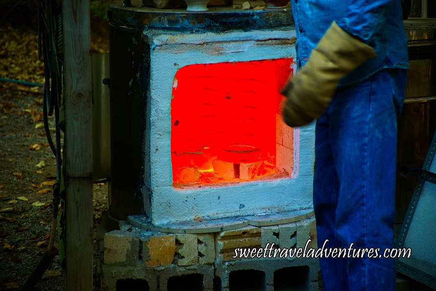 A Small White Kiln on Top of Bricks With Wares Inside the Kiln Which Are A Dark Orange Molten Colour