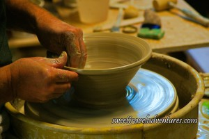 Hands Smoothing Out the Edge of a Large Bowl on a Pottery Wheel Inside a Plastic Container