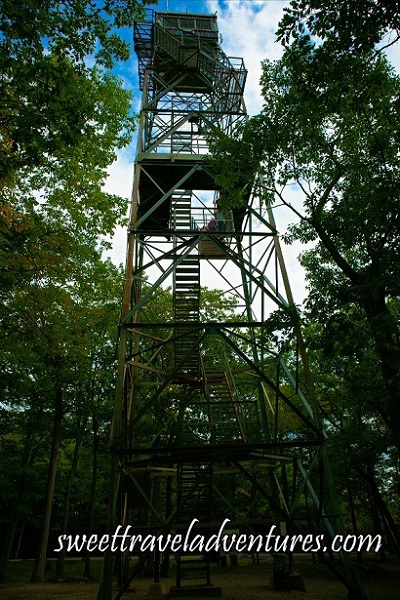 Side View of a Tall Metal Tower With a Staircase Through the Middle and a Small Enclosed Area on the Top, Surrounded by Green Trees, Blue Sky With Many Fluffy White Clouds