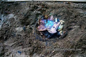 Shiny Blue, Rose, and Gold Metallic Coloured Maple Leaf Shaped Dish With Newspaper Under it, Laying in a Brown Dirt