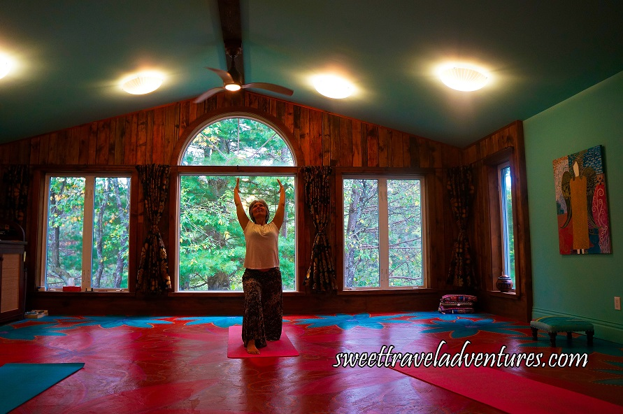 Front View of a Woman in Crescent Moon Yoga Pose, Standing on a Pink Yoga Mat on a Dark Orange Floor With Large Blue Flowers and Large Pink Flowers, Large Windows Behind Her With Wood Paneling and Curtains Pulled Back, a View of Green Trees, A Blue Wall on the Right With a Multi-Coloured Painting and Blue Ceiling With Four Glowing Lights and a Ceiling Fan in the Middle
