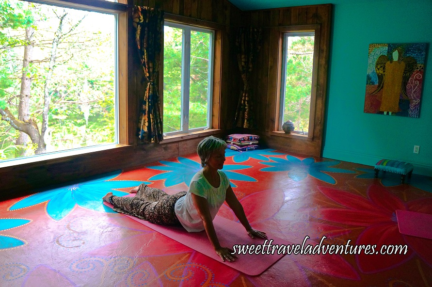 Angled Side View of a Woman Lying on a Pink Yoga Mat in Cobra Pose on a Dark Orange Floor With Large Blue Flowers and Large Pink Flowers, Large Windows With Green Trees Outside Behind Her, And a Blue Wall With a Multi-Coloured Painting on it