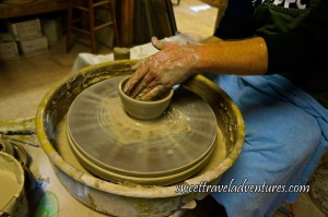 A Hand Smoothing Out a Small Bowl on a Pottery Wheel in a Plastic Bowl With Excess Clay