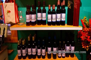 Two Shelves of Dessert Wines, on the Top Shelf on the Right End are Two Wine Boxes, One Brown and One Red, at the end of the Left Side is a Glass Decanter