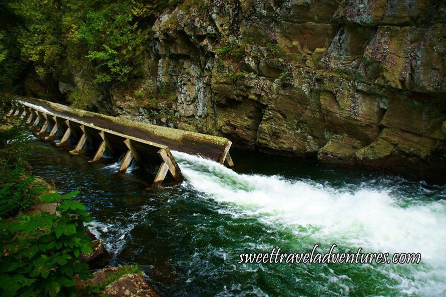 A Long Wooden Open Structure With White Water Rushing Through it, Wooden Structure is in a River With Large Brown Rock and Green Plants on Both Sides of the River