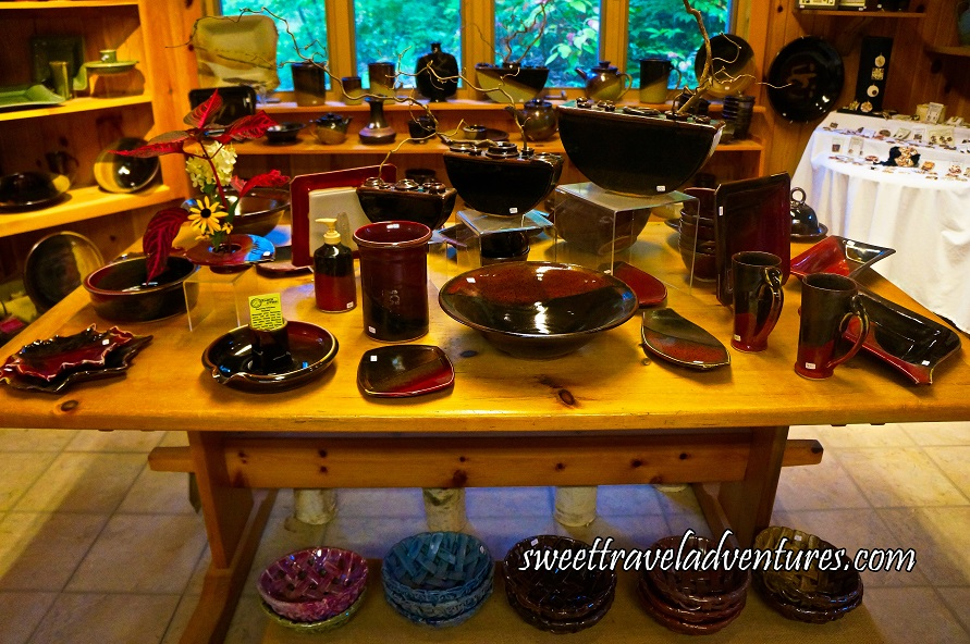Various Pottery Pieces on Wooden Table and Under the Table, and Behind the Table Various Pottery on Shelves, a Side Table, and the Wall, and Jewellery on a Table With White Linen on the Right