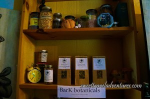 Botanicals in Glass Jars and Brown Paper Bags on Wooden Shelves