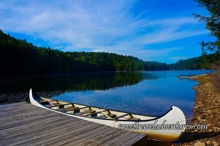 A Bright Blue Sky With Streaks of White, Several Green Trees Around a Blue Lake and Reflecting on it, a Wooden Dock Angled to the Left With a Long White Canoe Next to it, the Edge of a Shore to the Right With Dirt and Rocks