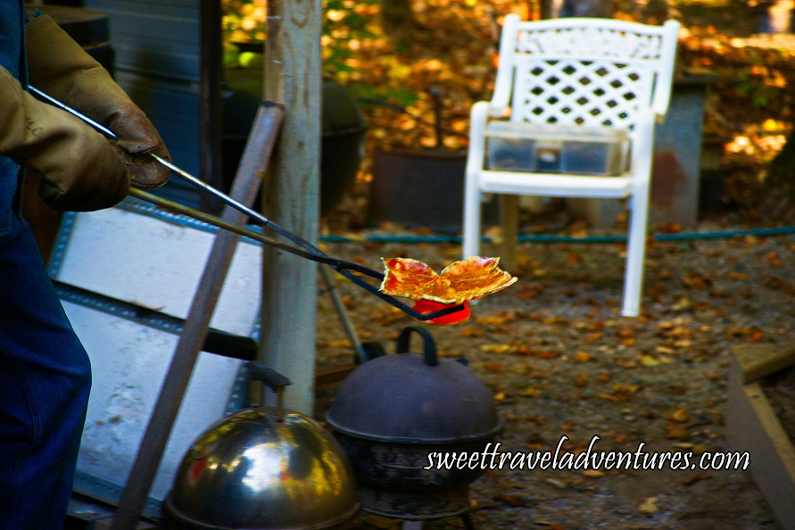 A Maple Leaf Shaped Dish With Dark Orange/Golden Molten Glaze Being Held by Two Long Tongs, Partial View of a Person Holding the Tongs Wearing Heavy Tan-Coloured Gloves and Blue Jeans, is Outside With Yellow Leaves on the Ground and a White Chair in the Background, There are Two Pots With Round Lids and a Handle on Each Lid, One Pot Silver and the Other Black, Pots are on the Ground Underneath the Dish and Tongs