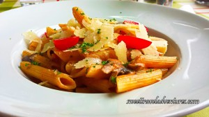 Penne With Mushrooms, Half-Cut Cherry Tomatoes, Pieces of Parmesan Cheese, and Herbs in a White Pasta Bowl on a Table With a Checkered White, Red, and Green Tablecloth