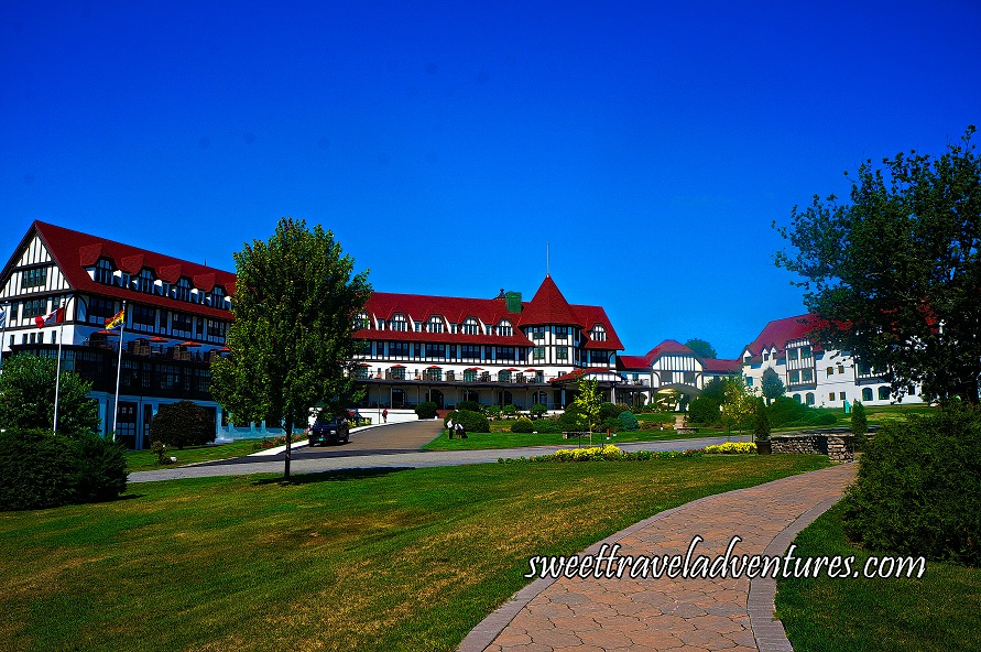 A Huge White Castle-Like Hotel With a Red Roof and Manicured Lawn With Green Trees and Shrubs, a Driveway Around the Front of the Hotel, and a Walkway to the Right Leading to the Hotel, With a Blue Sky
