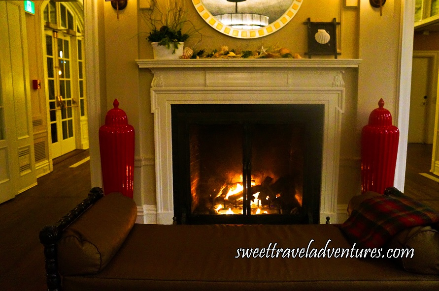 A Large Fireplace With Glass Doors, White Molding Around it and a White Mantle, a Round Mirror Above the Fireplace on an Off-White Wall, a Brown Leather Lounge Chair in Front of the Fireplace With a Red Checkered Throw