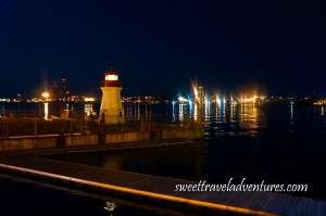 A Small Red and White Lighthouse Lit Up at Night With a Wooden Dock Leading Towards it and Open Water and Multi-Coloured Lights Behind the Lighthouse