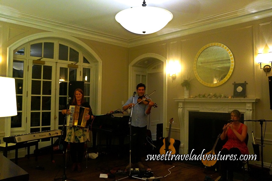 A Man Playing a Fiddle, on the Right is a Woman Playing the , on the left is a Woman Playing the Accordian, and Other Musical Instruments Around Them, They are Playing in Front of a White Fireplace in a Building With Off-White Walls and White Trim and Dark Brown Hardwood Floor