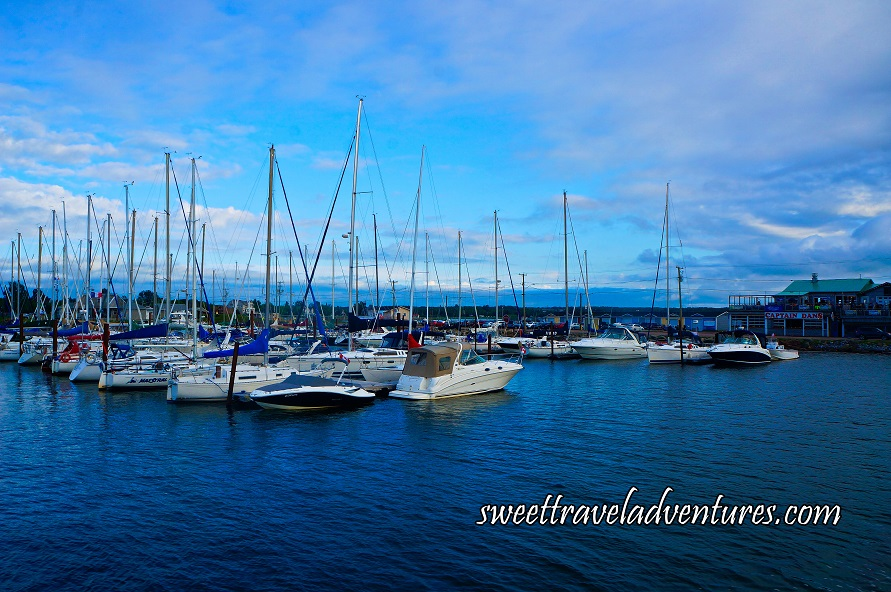 Sailboats, Speedboats, and Yachts Docked in the Water With a Wharf Behind and a Blue Sky With White Fluffy Clouds at Dusk