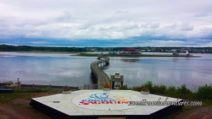 """A Hexagon With the Words """"La Pays de la Sagouine"""" Written in the Middle, a Wooden Curved Bridge Across Calm Water to an Island With Colourful Buildings and a Lighthouse, in the Distance is Land With Green Grass, Trees, and Buildings, and a Blueish Grey Sky With Fluffy White Clouds"""