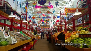 Red Stalls With White Lamps Hanging Down With Fresh Produce on the Right and Packaged Foods on the Left and Colourful Mobiles Hanging From the Rafters