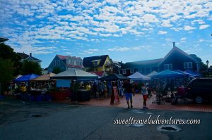 Pavement in the Front, Then Several People at a Cobblestone Square With Small Square Shaped Peak Tents of Different Colours With Covered Tables Underneath With Tablecloths of Different Colours and Things on Top of the Tables, Houses and Buildings in the Background of Different Colours, a Dark Vehicle on the Right, Green Trees on the Left, and a Blue Sky With Many Many Small White Clouds